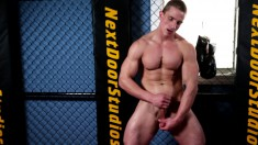 Muscled beefcake Marcus leans back on a balance ball to stroke his cock