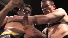 Two muscled studs in black leather insert thick rods into their hard cocks in a sounding session